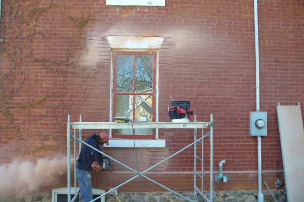 Photo of worker cutting away brick